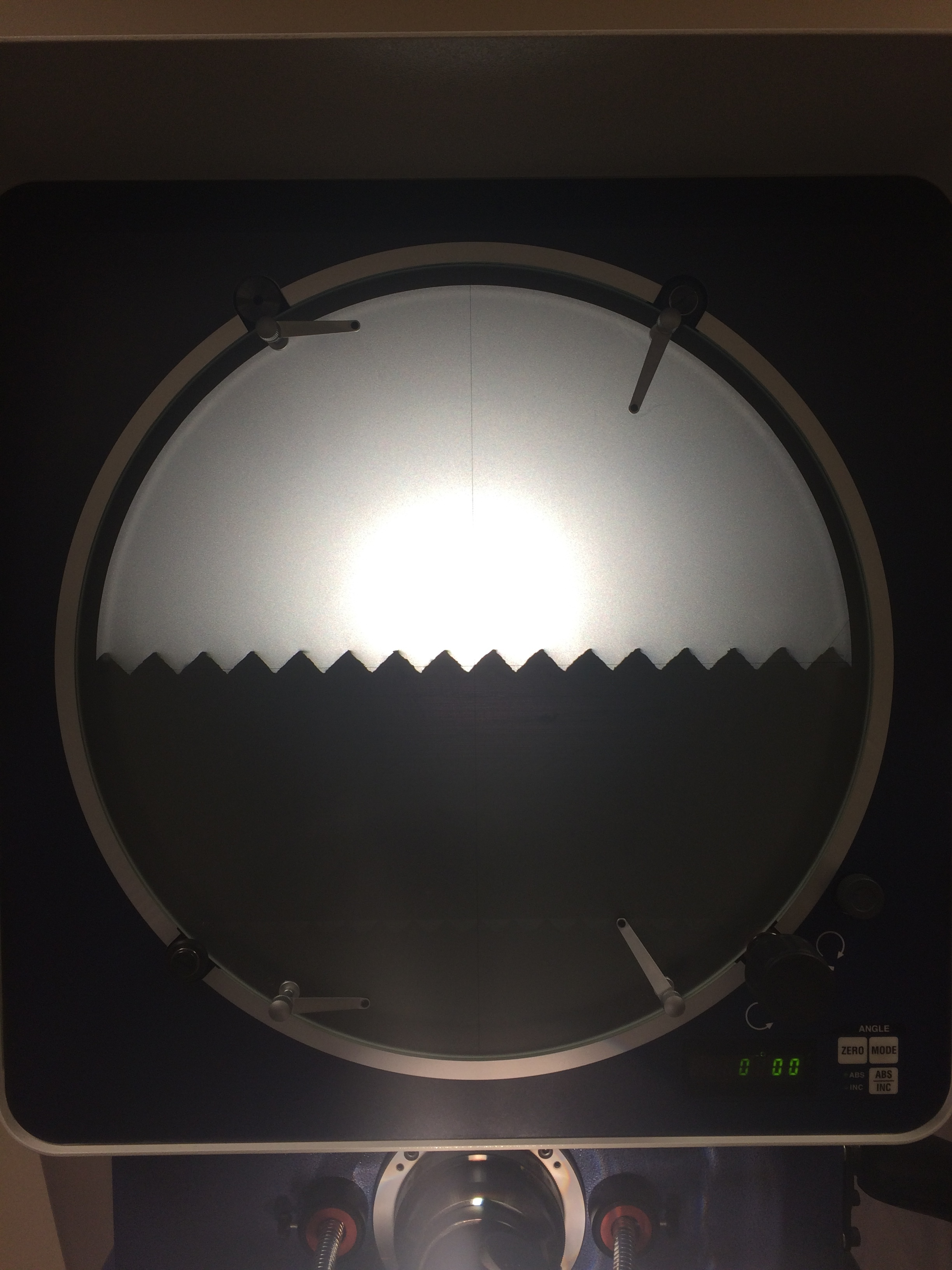 These are the teeth of one of the microbend gratings seen on a comparator. The comparator was used to verify the tooth profile and pitch of the teeth.