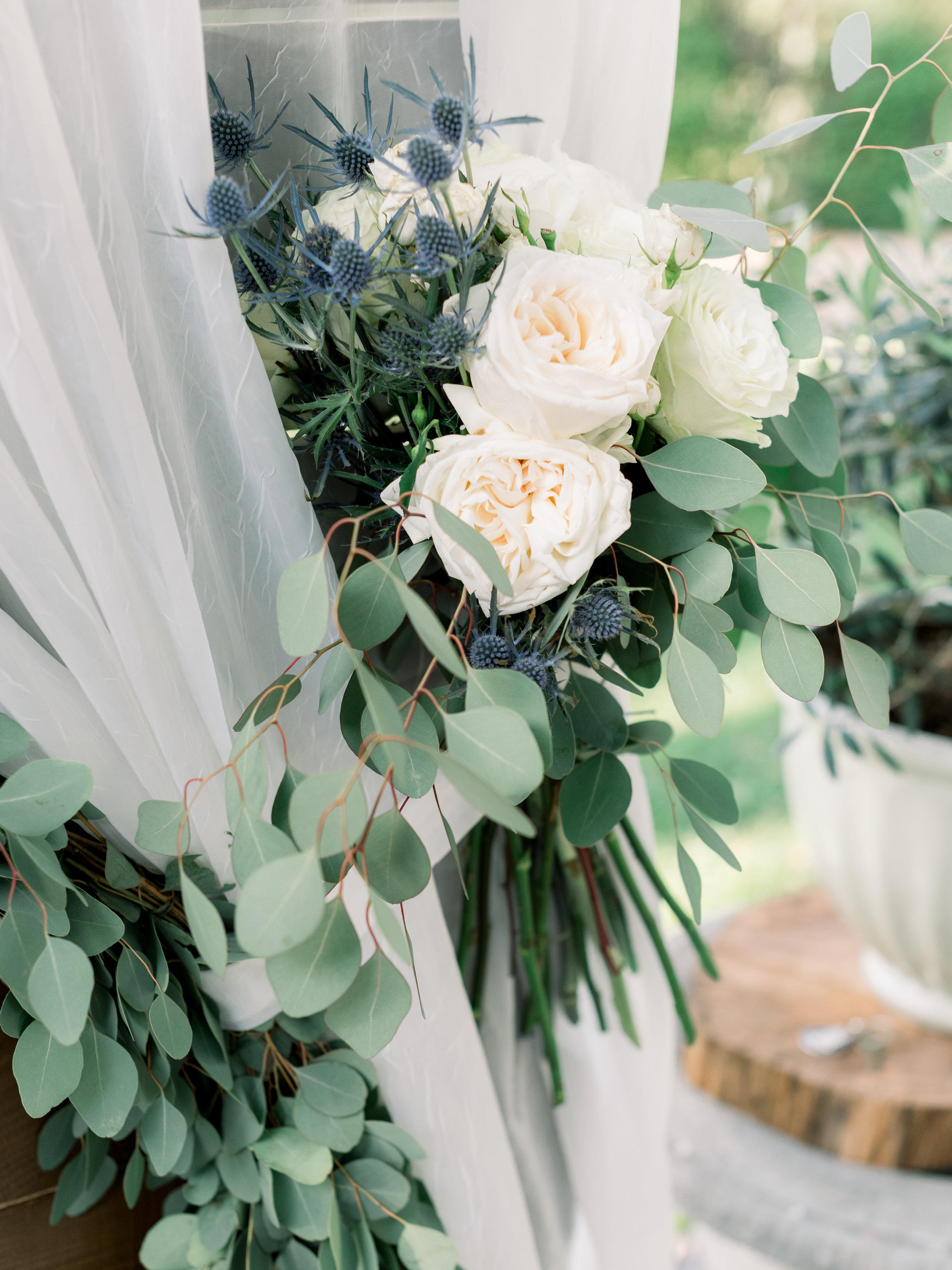 cream-rose-and-blue-thistle-garland-wrapped-around-wedding-altar.jpg