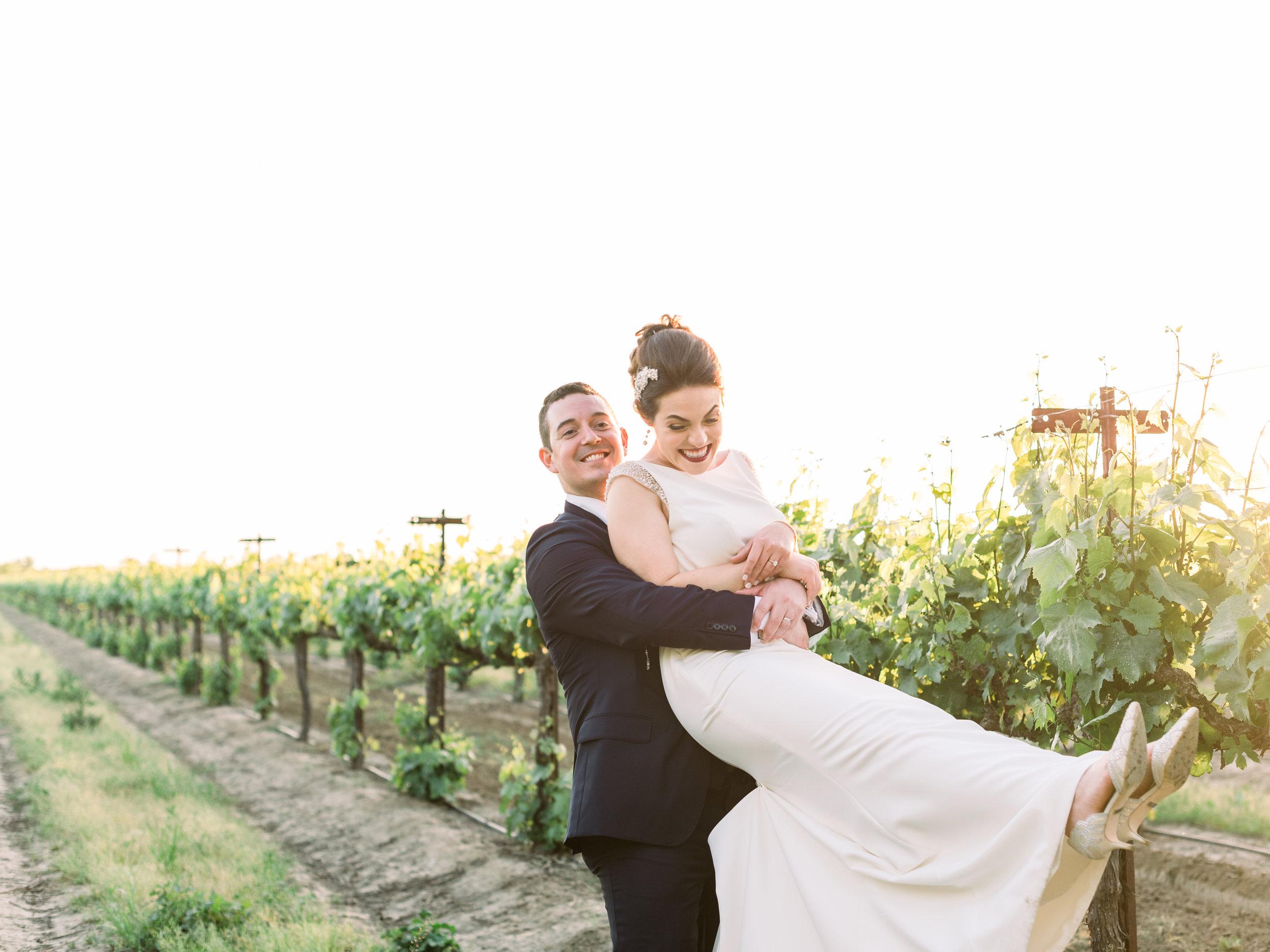 bride-and-groom-being-playful-in-the-vineyard.jpg