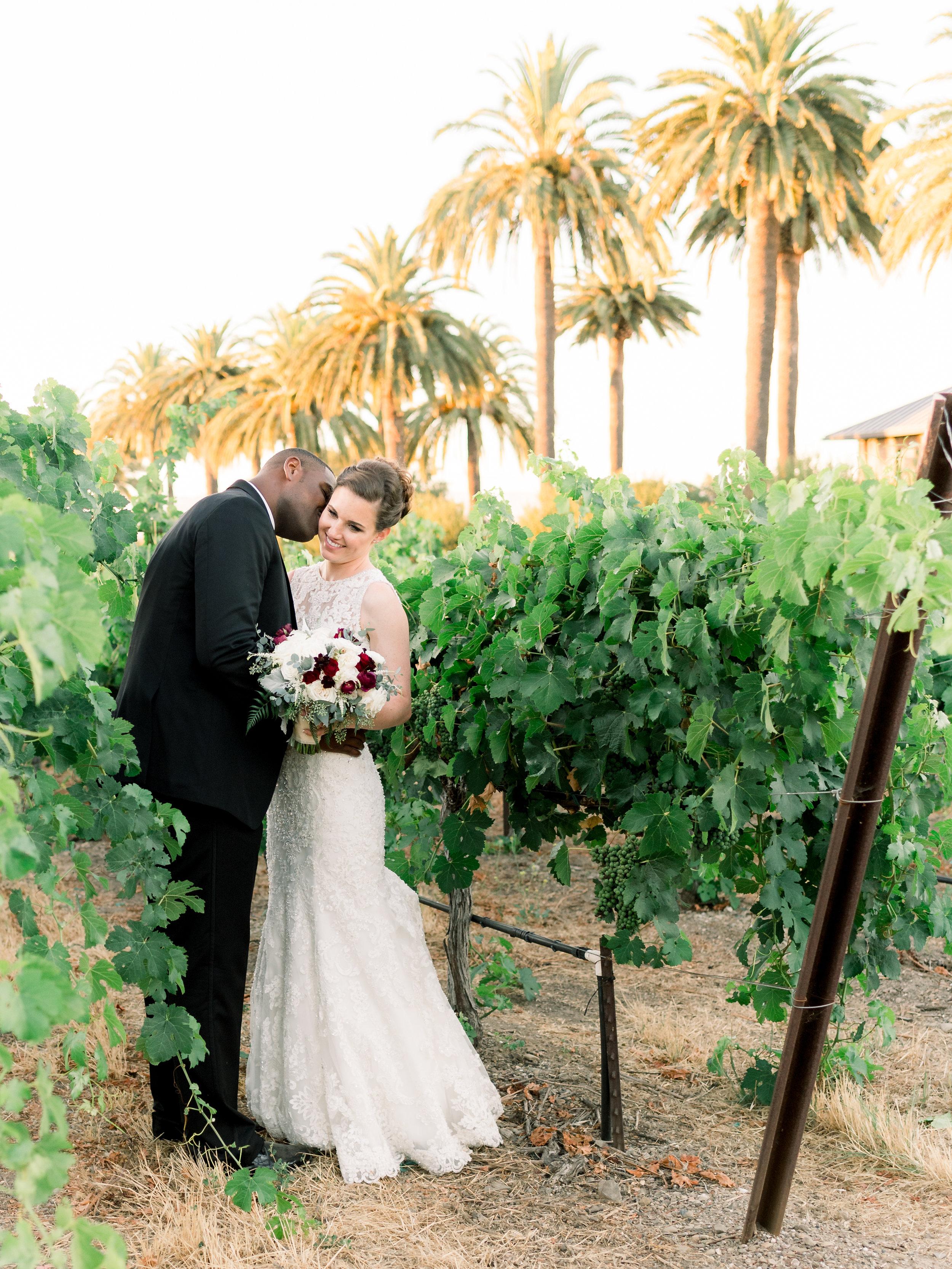 groom-kissing-the-bride-in-the-vineyard.jpg
