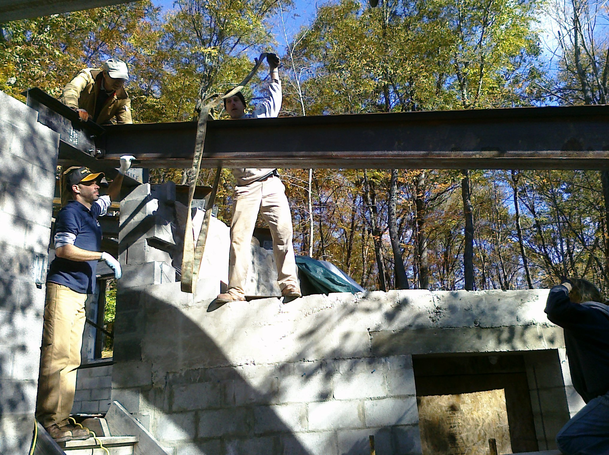 Patrick Toon, Pete Fisher, & Jim Reilly attach a roof beam to the stairway lintel.