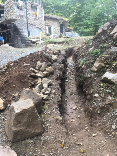 This trench will contain the conduit and wire that bring electric service to Underhill. We're digging this one by hand - and lifting out the boulders using an ancient method.