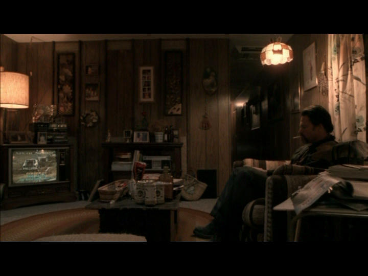 Rough working class interior of Leroy McKinney's (Tim Daly) trailer home.