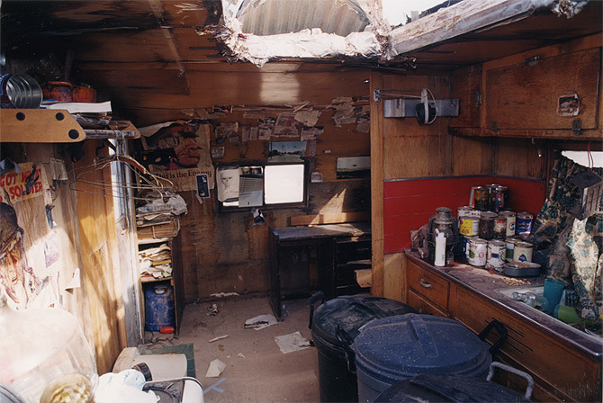 A reverse shot of the squalid interior of the abandoned UFO fanatic's trailer.