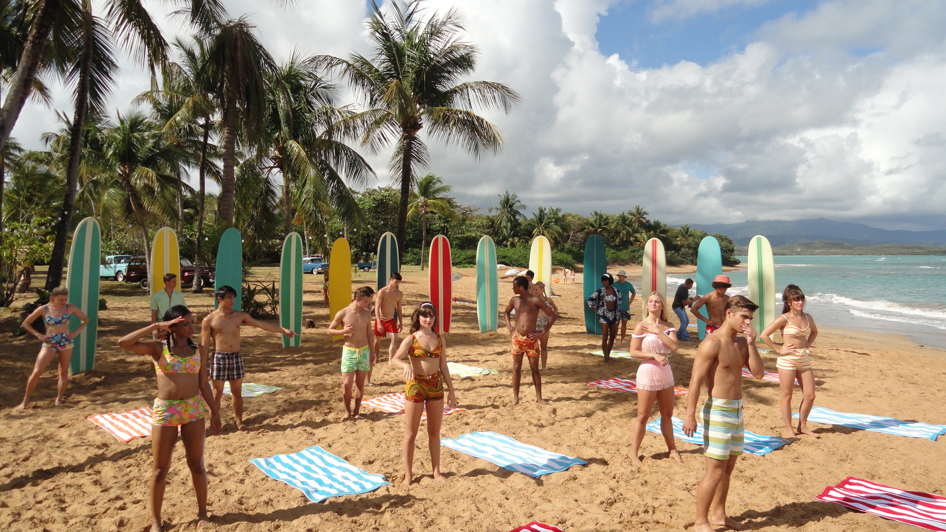 """Teen Beach Movie is a film within a film, in which two contemporary kids (Ross Lynch and Maia Mitchell) are sucked through a wormhole into a Frankie and Annette-style beach musical set in 1962. Here in the 1962 period is the """"cast"""" of the film within the film preparing to dance among a few of the more than 100 custom surfboards we had made."""