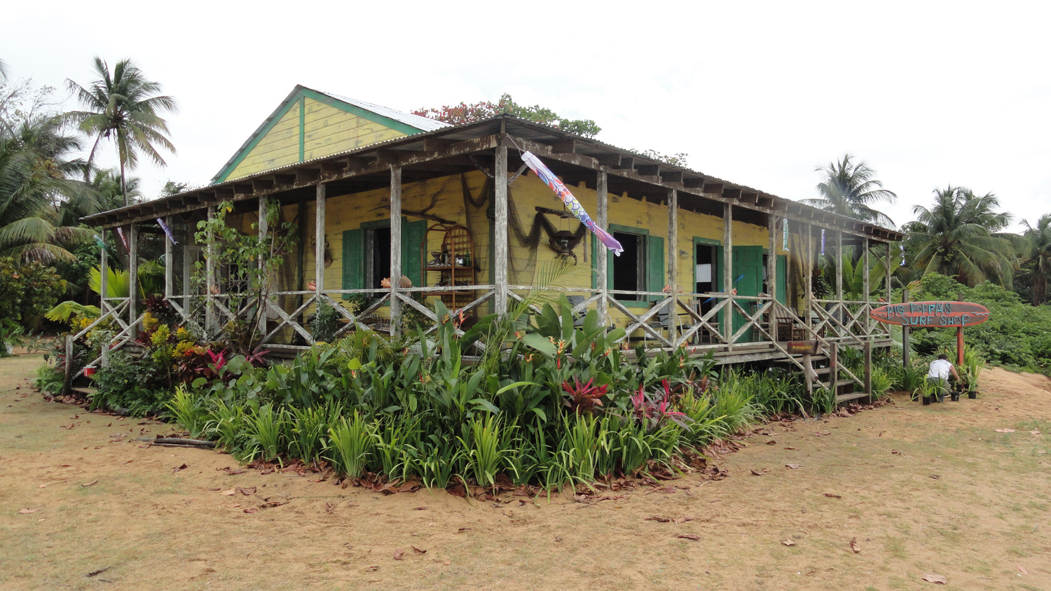 The beginning and end scenes in Teen Beach Movie take place on the same beach as the 1962 period scenes, but in modern times. This is Big Poppa's (Barry Bostwick) surf shop, a home and workshop he shares with his grandaughter McKenzie (Maia Mitchell). After the 1962 portion of the shooting schedule was complete, we had just six days to tear down Big Momma's exterior, and build this interior/exterior house, complete with dressing and greens before the company returned to complete shooting.