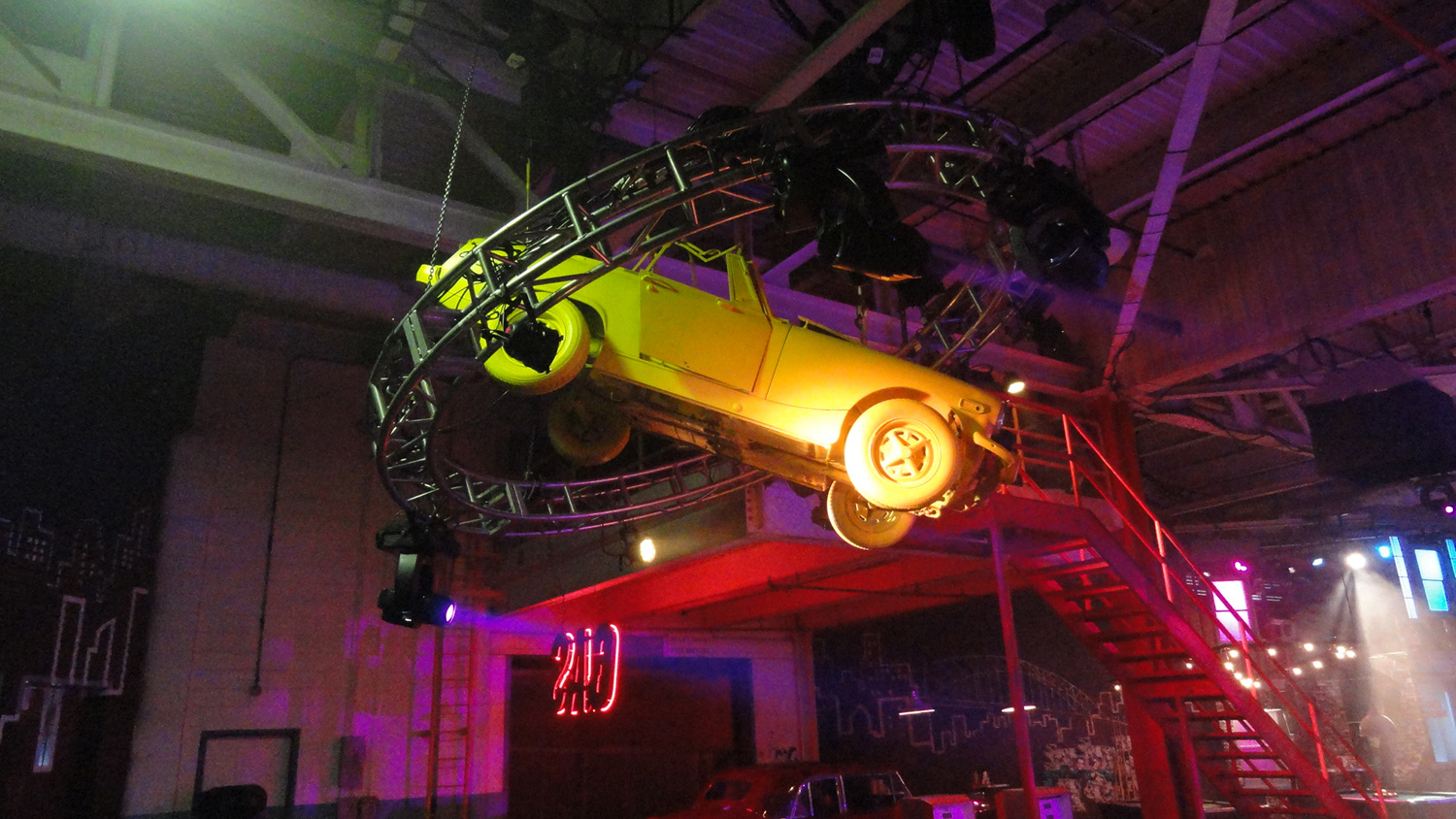 As part of our de-construction concept, we found lightweight, junked English cars, stripped them down to the bare bones, and hung them from the ceiling, ringed by circular lighting trusses.