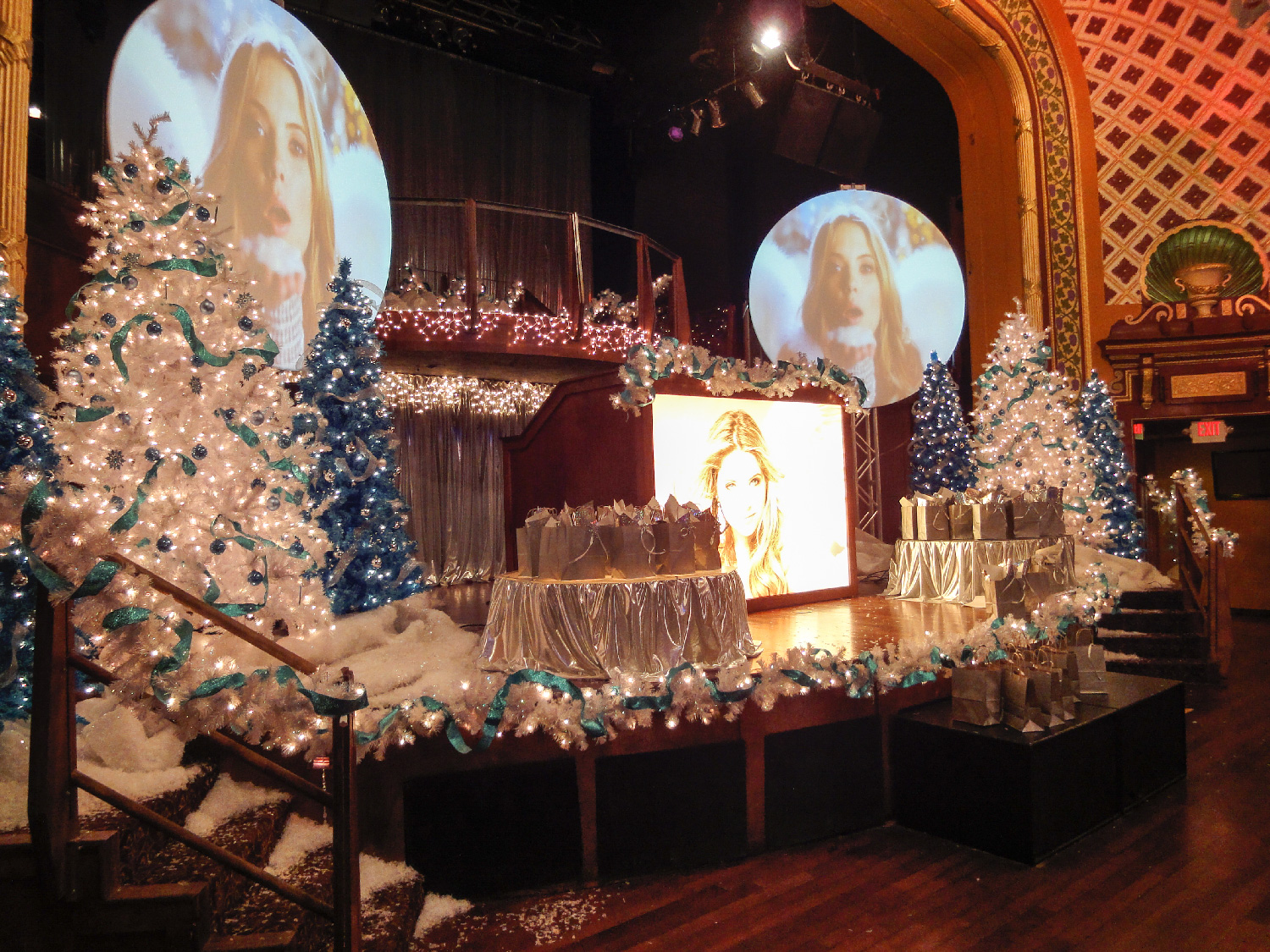 "Detail of stage at venue with projection of scenes of ""Snow Angel"" (Ashley Benson), a movie within the story that was never shot. We created a loop of scenes from the movie for the memorial."