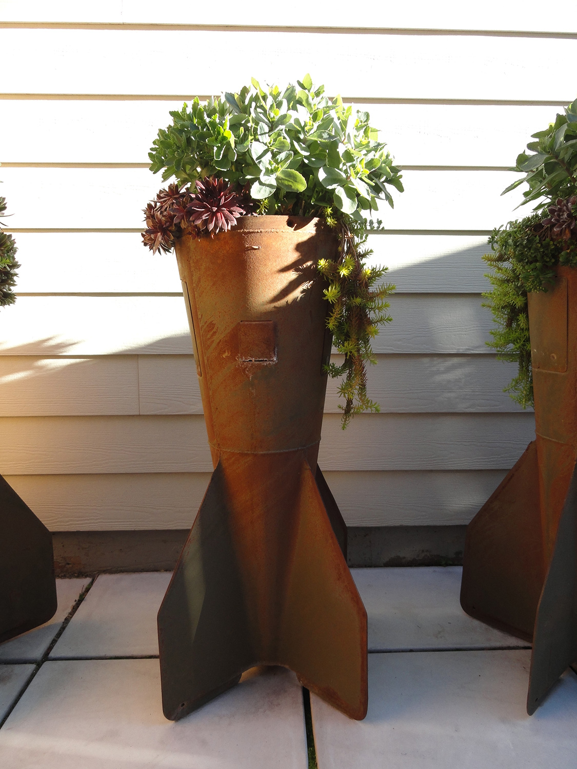Second World War salvaged 500 lb. bomb-tails modified for succulent container gardens.