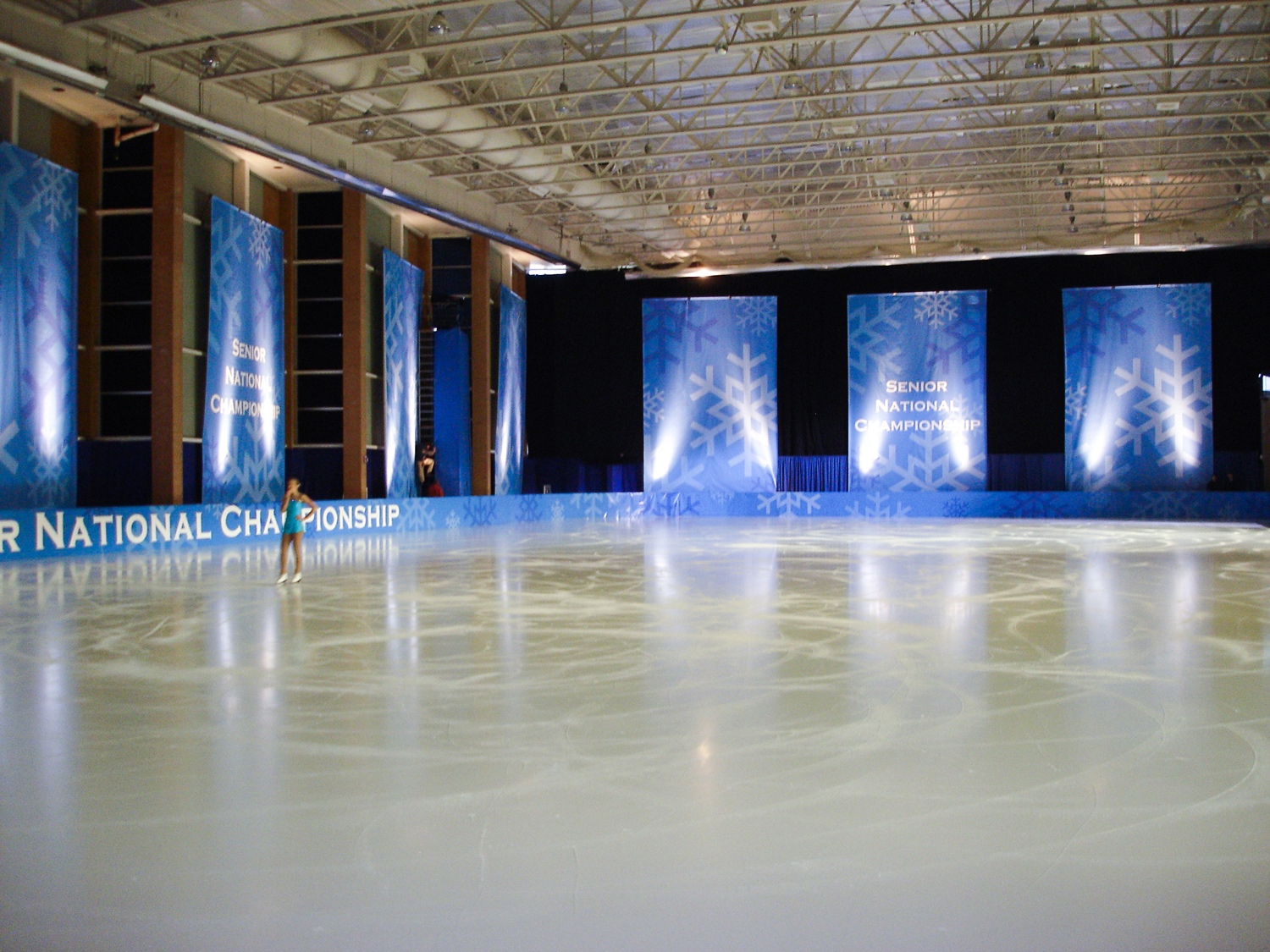 This photo shows a major national figure skating championship. We painted the hockey rink pure white, removed all the protective glass, and created huge wintery graphics to drape the walls and beautify the dasher-boards.