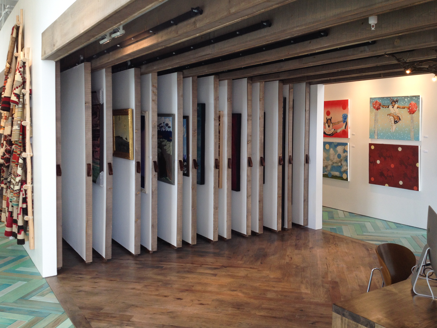The gallery has a huge collection of art, well beyond the hanging capacity of gallery space. We custom built these art storage walls to address that need. Easily moveable by customers, they can potentially store up to 100 pieces.