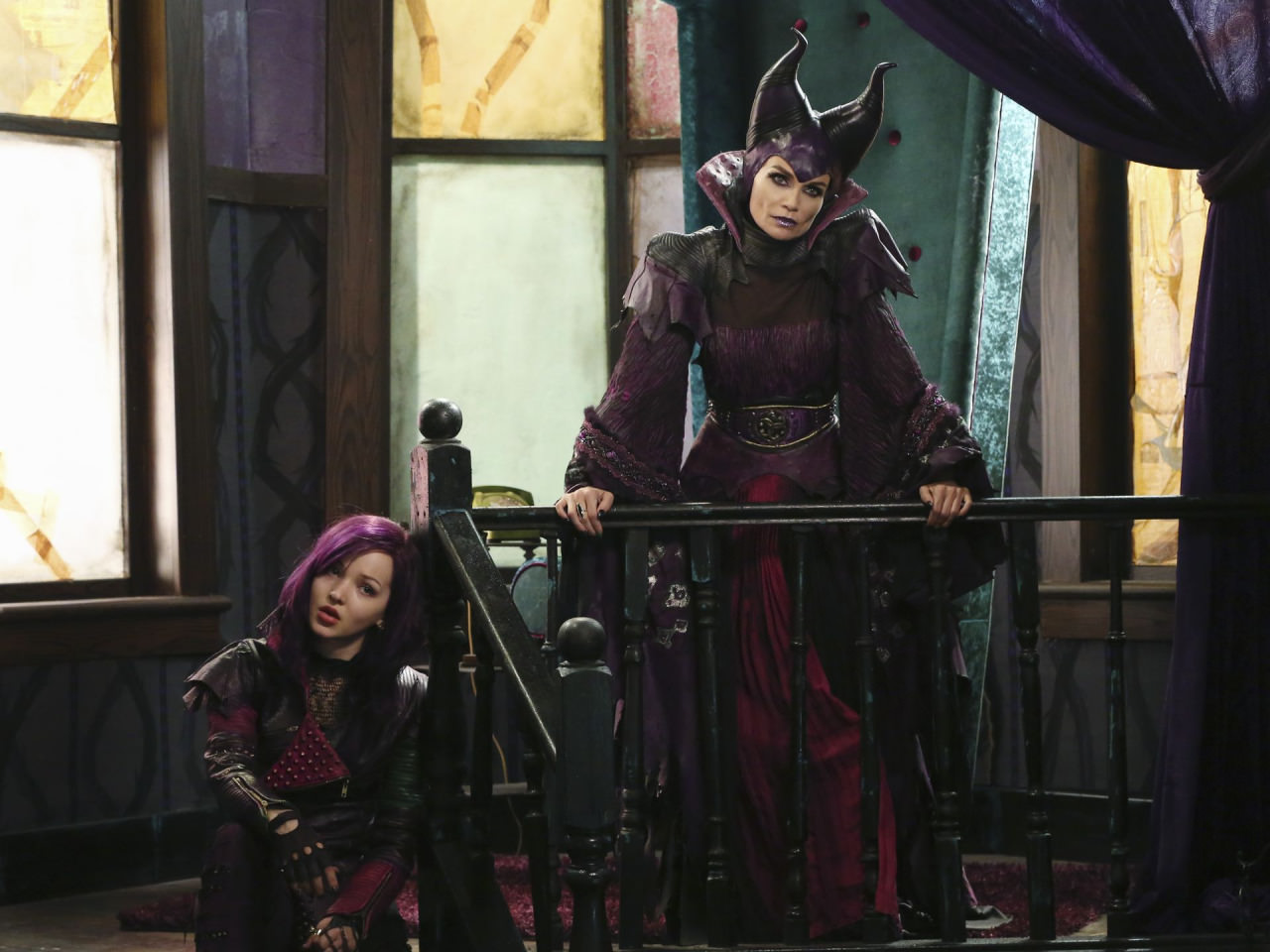 Mal (Dove Cameron) broods below her imperious mother Maleficent (Kristin Chenoweth) in her ratty apartment on the Isle of the Lost.  (Disney Publicity photo)