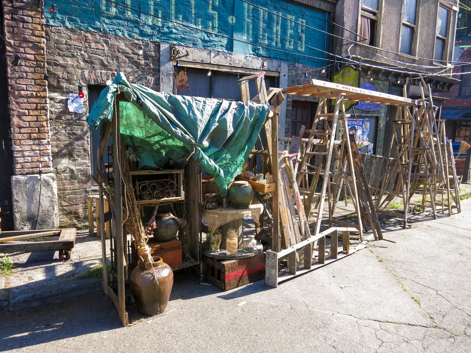 Street detail of vendor's shacks on the Isle of the Lost. The vendor on the right of frame specializes in broken ladders.