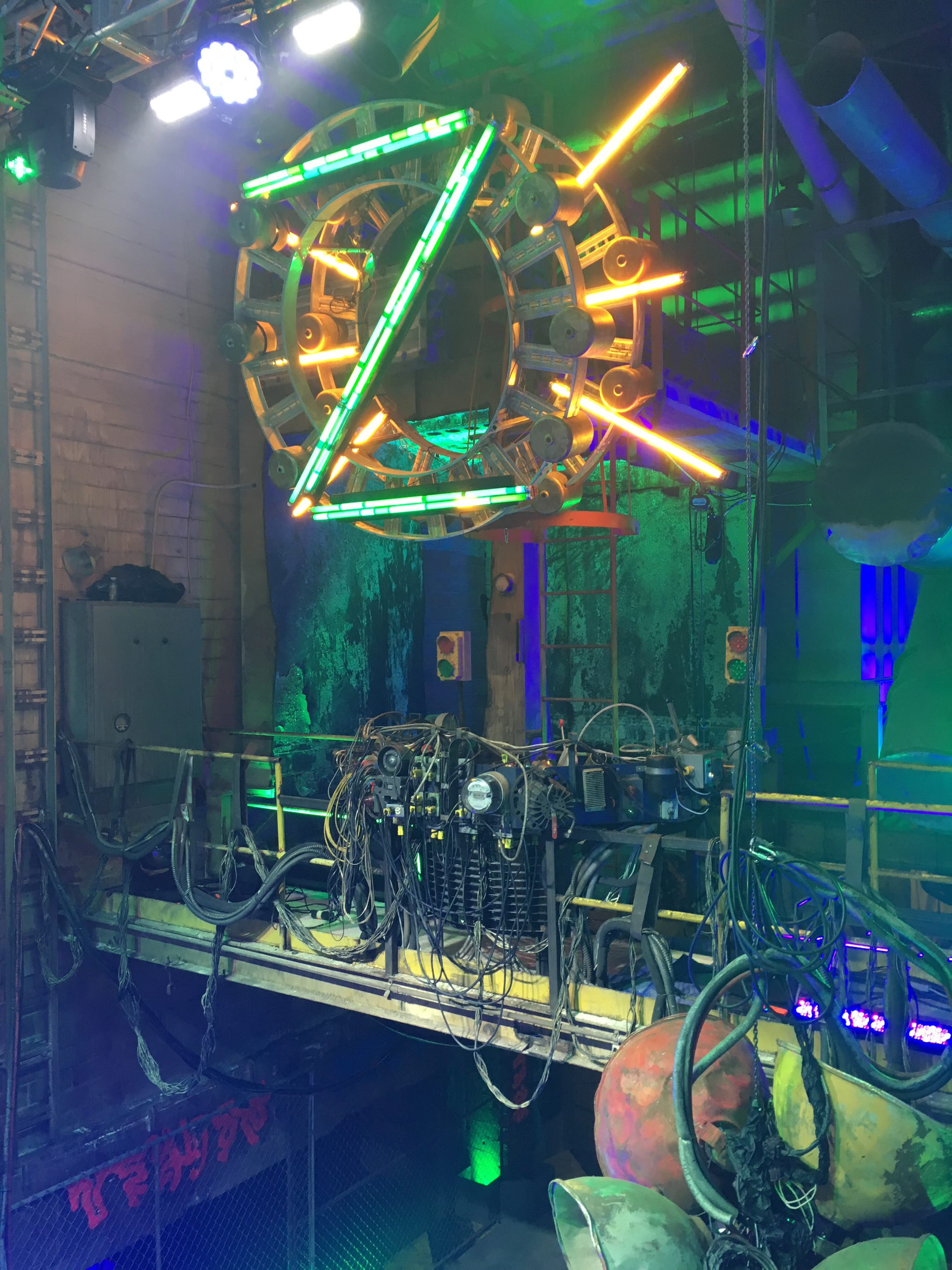 "The green zombie ""Z"" hangs above Eliza's (Kylee Russell) light control booth on a catwalk over the dance floor."