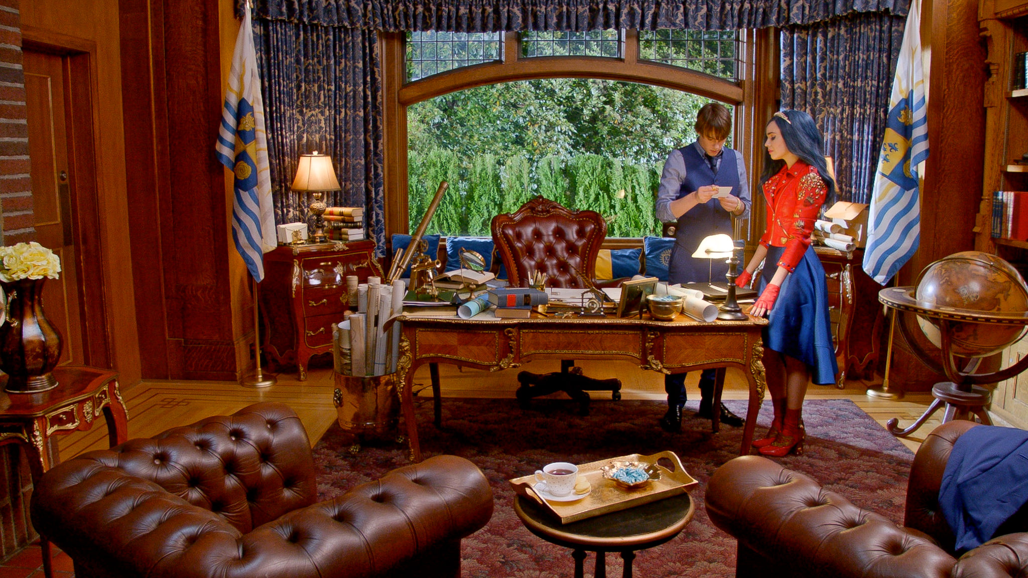 Now the King of Auradon, young King Ben (Mitchell Hope) has an office befitting his station. Here Evie (Sofia Carson) brings Ben bad news.