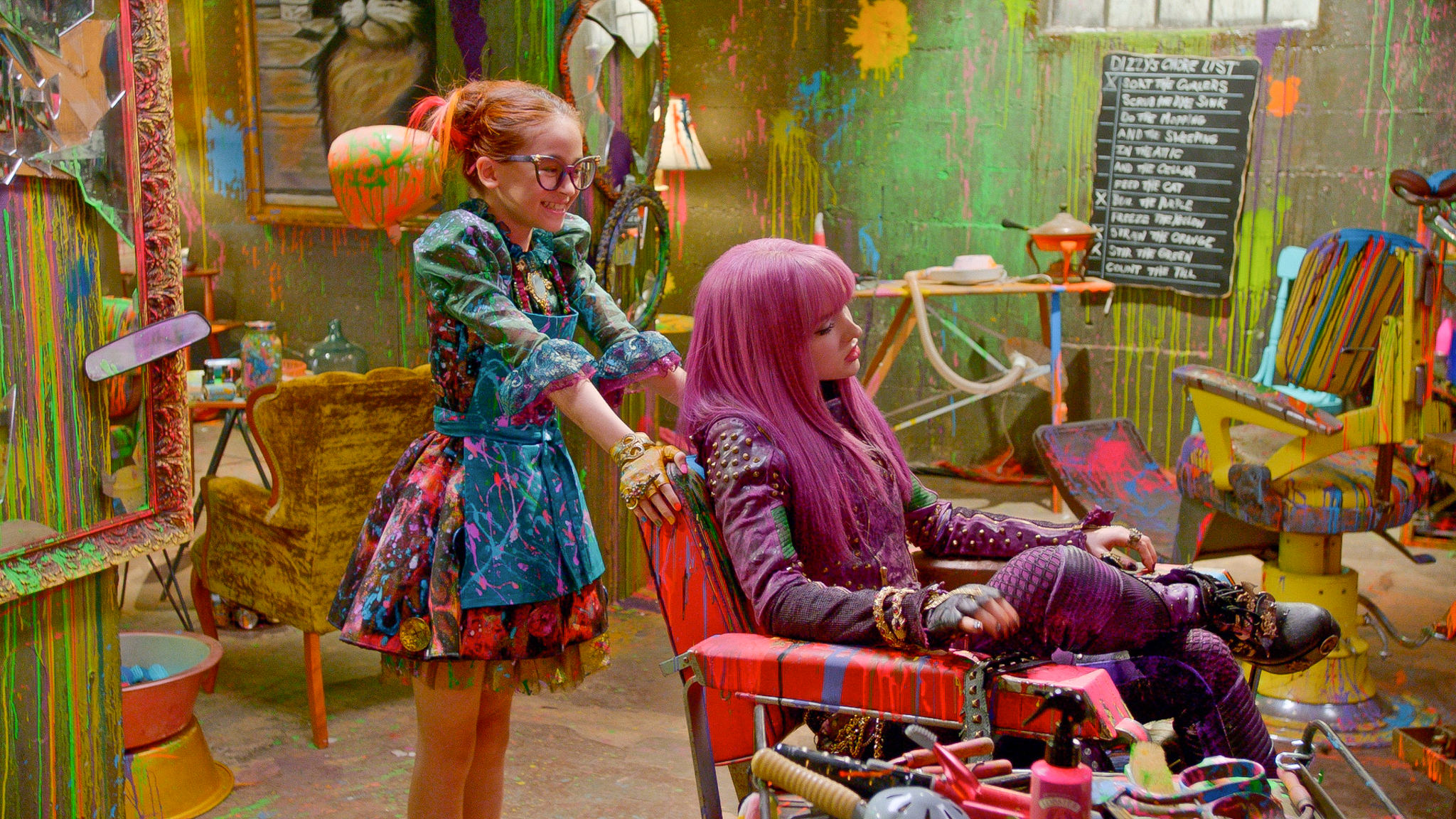 Mal (Dove Cameron) Gets a consultation from Dizzy (Anna Cathcart) in the madness of Drizella's Curl Up and Dye on the Isle of the Lost.