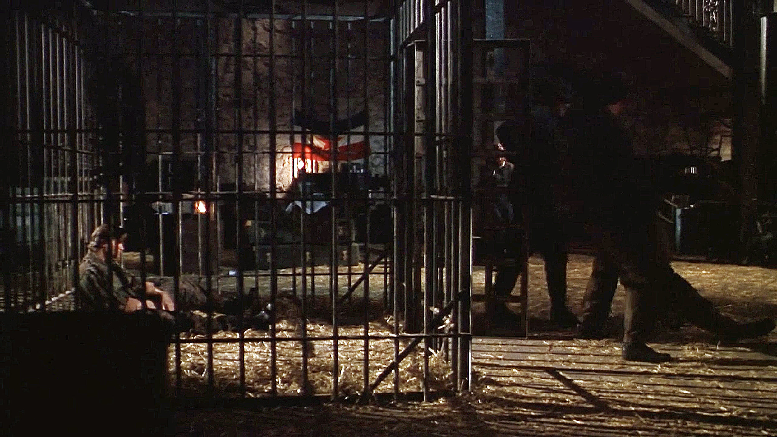 American Mercenary Karl (Treat Williams) plots his escape from his animal cage.