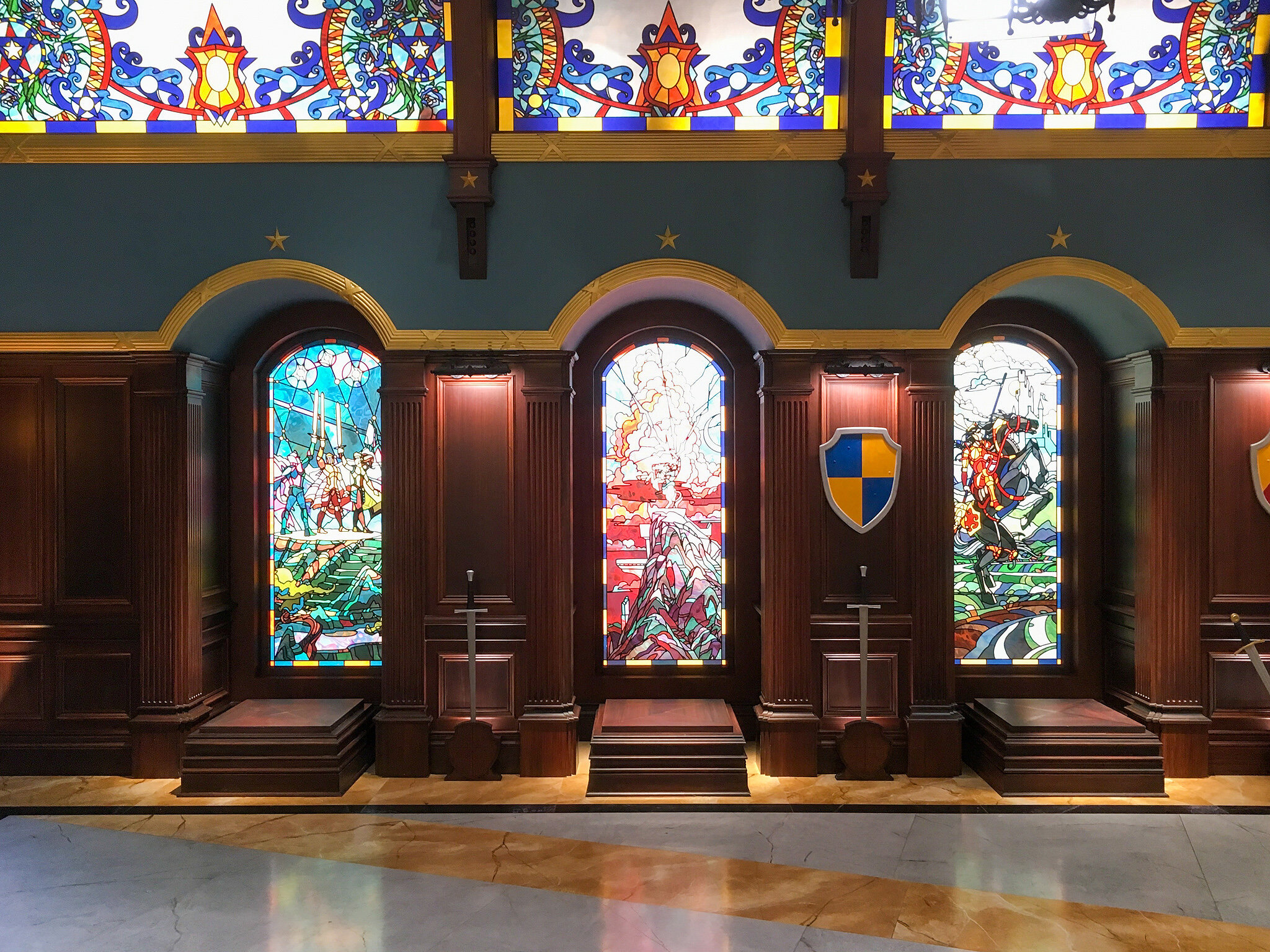 There were 13 niches to display the suits of armor in Auradon's royal palace armory and each one was backlit by a stained glass window with a unique narrative of mythical chivalry.