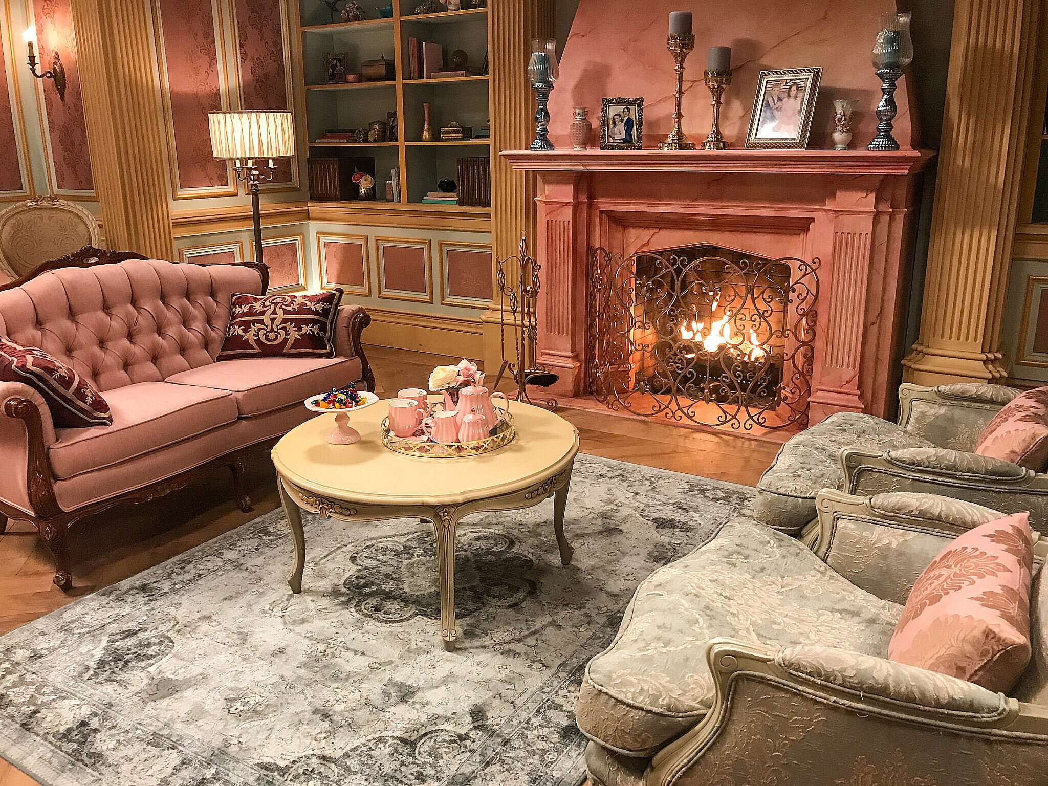 A detail of the functioning pink marble fireplace and sitting area in Audrey's bedroom set.
