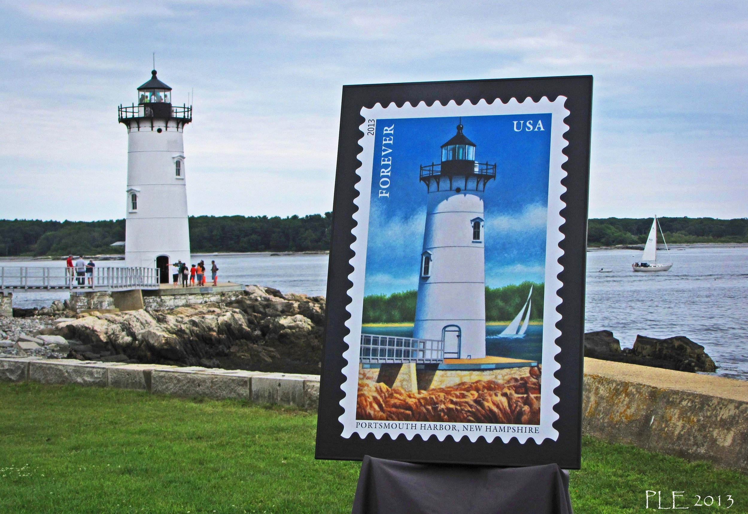 """NEW HAMPSHIRE    Portsmouth Harbor Lighthouse Stamp – First Day of Issue Ceremony New England Today - Yankee Magazine - April 28, 2014   I was quite excited to learn that Portsmouth Harbor Lighthouse has been chosen Editors' Choice for Best Lighthouse in the May/June issue of the Yankee Magazine Travel Guide to New England.  Portsmouth Harbor Lighthouse is a short drive up the coast from my house here in Southern New Hampshire. I have visited it on land often and have passed by it on the ferry when heading out to the Isles of Shoals many times. It is a well-known, and much loved icon on our NH coastline.  So, it was a proud day on Saturday, July 13, 2013, when the US Post Office commemorated a postage stamp with the image of the lighthouse as part of a 5-stamp series called """"The Lighthouses of New England."""" A formal ceremony was held under a tent, on the lawn in front of the lighthouse. A large poster of the painting of the lighthouse, that was used as the artwork for the postage stamp, was unveiled.  After the ceremony, I asked one of the organizers if he would be willing to move the poster of the stamp outside to the lawn, so I could photograph it with the real lighthouse in the background. Just as I was getting ready to take the photo, a sailboat passed by, making my image look even more like the stamp!  I am planning to enter this photo in the 2014 """"My New England"""" Photo Contest, but thought you might like to see it now, since the lighthouse will be featured in your May/June issue.   Photographer: Patricia Lane Evans   Location: Seabrook, New Hampshire   https://newengland.com/today/travel/new-hampshire/portsmouth-harbor-lighthouse-stamp-first-day-of-issue-ceremony/"""