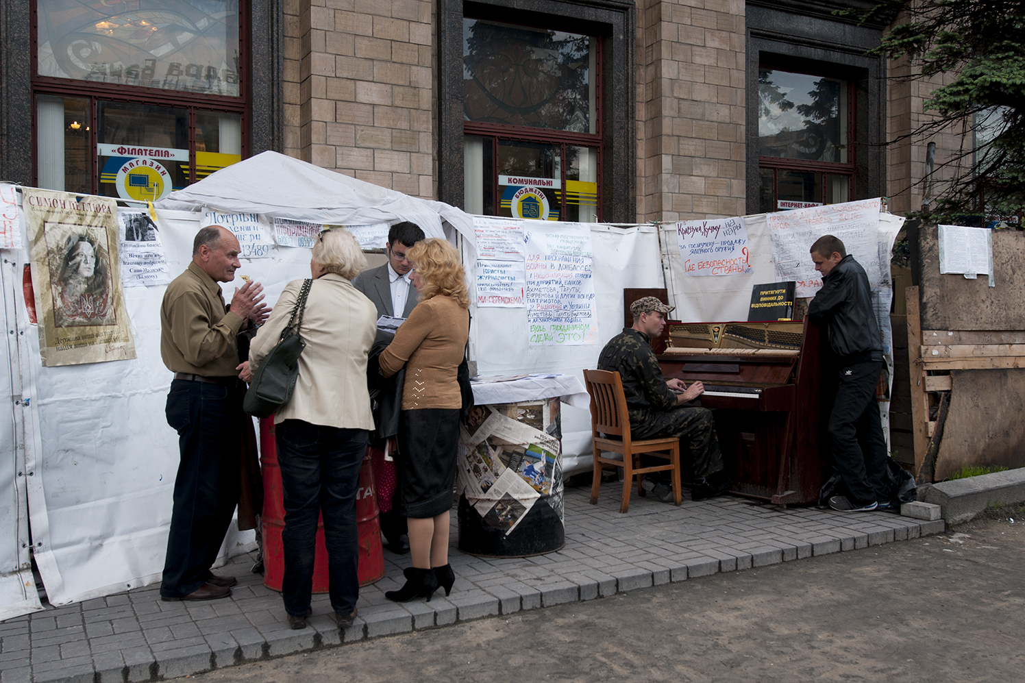 An activist in uniform playing the piano in front of the Media center of