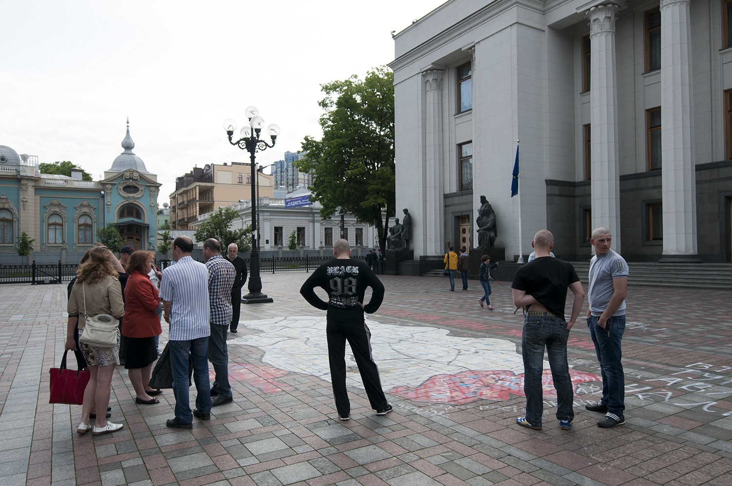 People standing over a map of Ukraine showing the areas under control of the Pro Russian Forces, with the names of three politicians accused of being partially responsible of the current situation