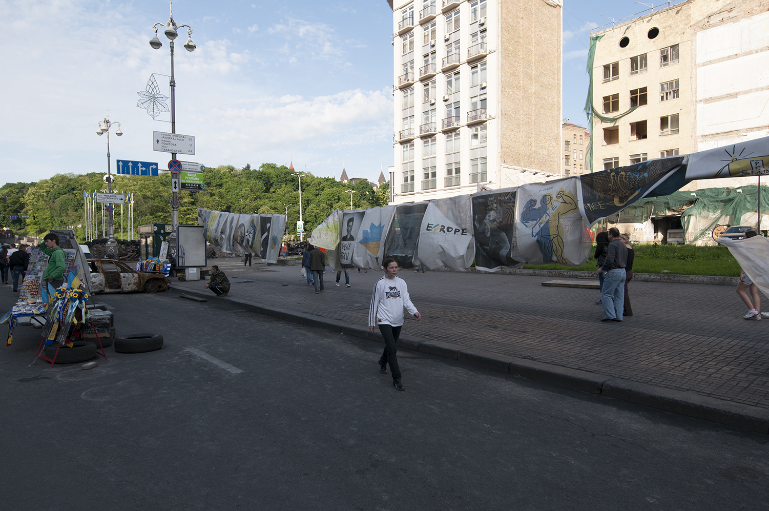 young girl walking past posters on Maidan