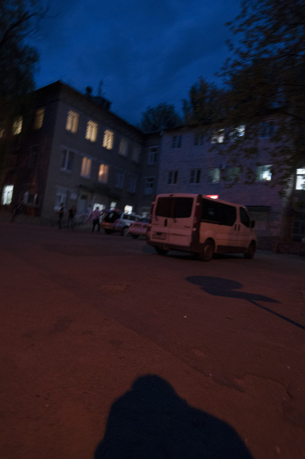 A man armed with a automatic weapon closing the trunk of his SUV while two other people watch over the people present in front of the downtown hospital's trauma unit, Donetsk.