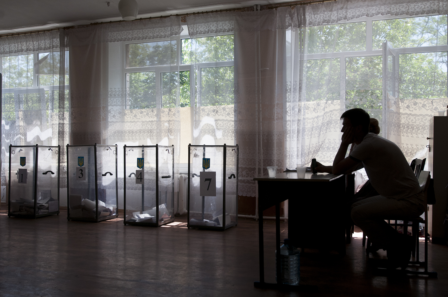 Peapole watching over the polling box from an empty polling stationinside a school of Mairupol