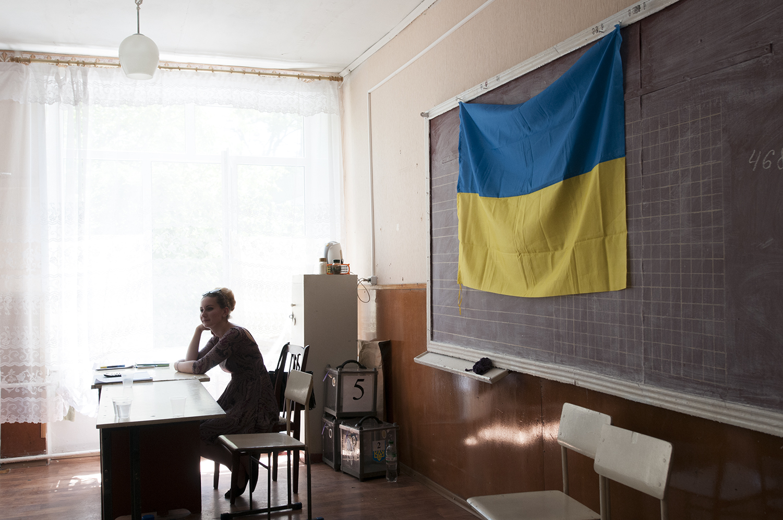 Ukrainian flag hanginside a school serving as a polling stationfor the dayElo, Mariupol