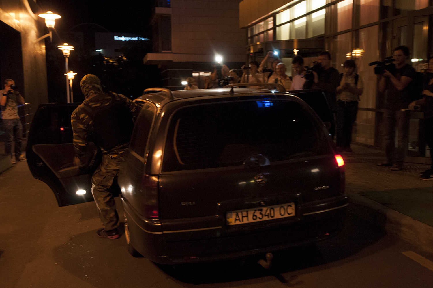 Tsarev's armed guard boarding a car in front of a crowd of journalist