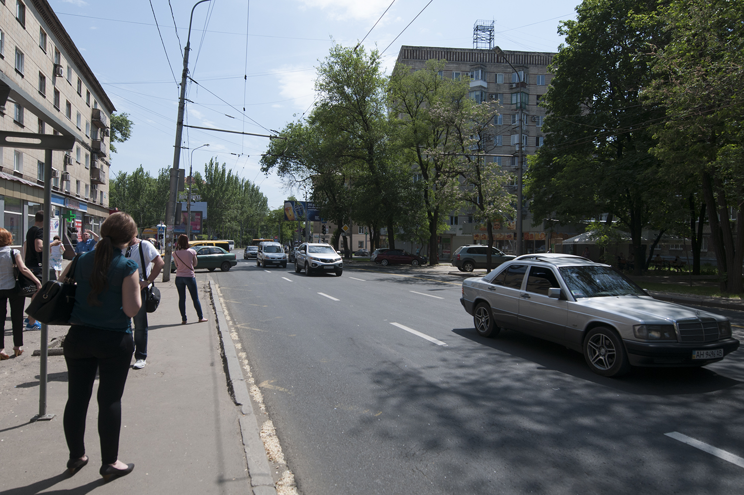 People waiting for the bus as the sound of the airport's bombing resound in the street of Donetsk