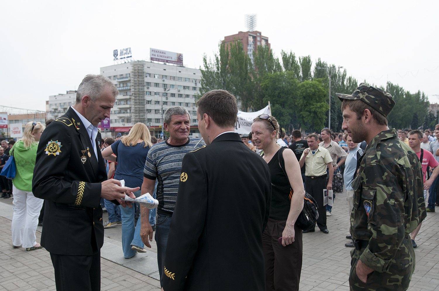 Miners in uniform speaking with demonstrators as an member of the Donetsk People's Republic Army