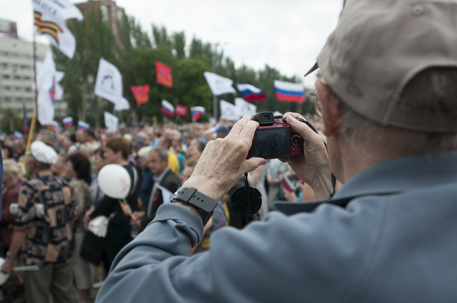 An elderly man taking pictures of the crowd at the Donetsk People's Republic meeting