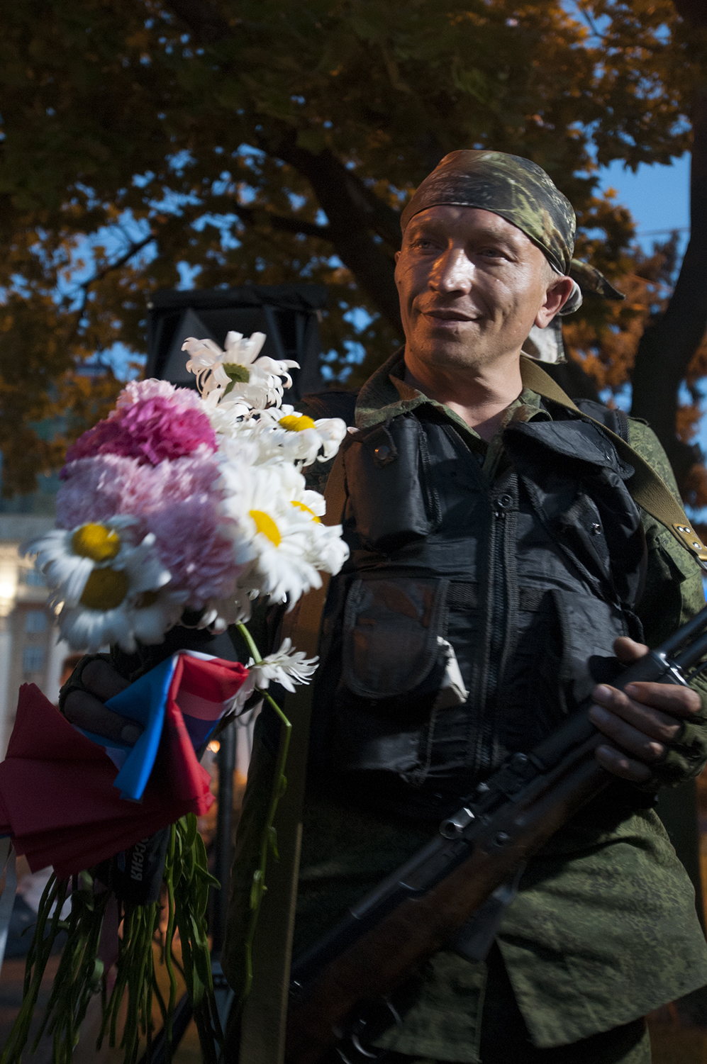 A separatist soldier holding his old rifle  from one hand and flowers warped in a Russian flag gifted by some women in the other one.