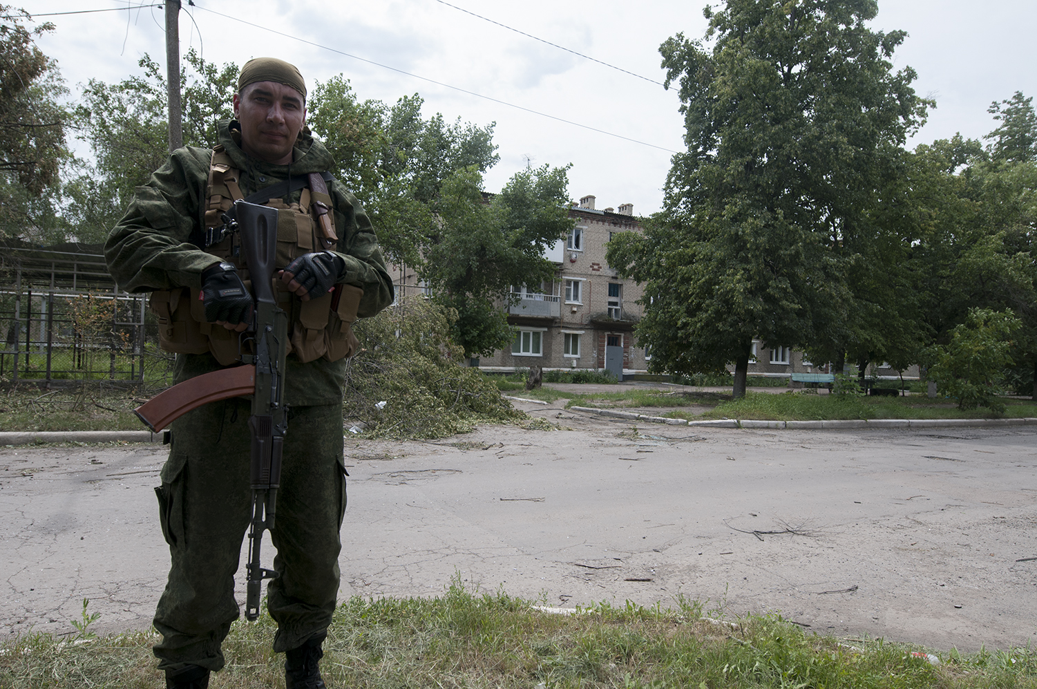 A separatist solider standing next to the damaged neigboourhood as mortar start to fall a few hundred of meters away