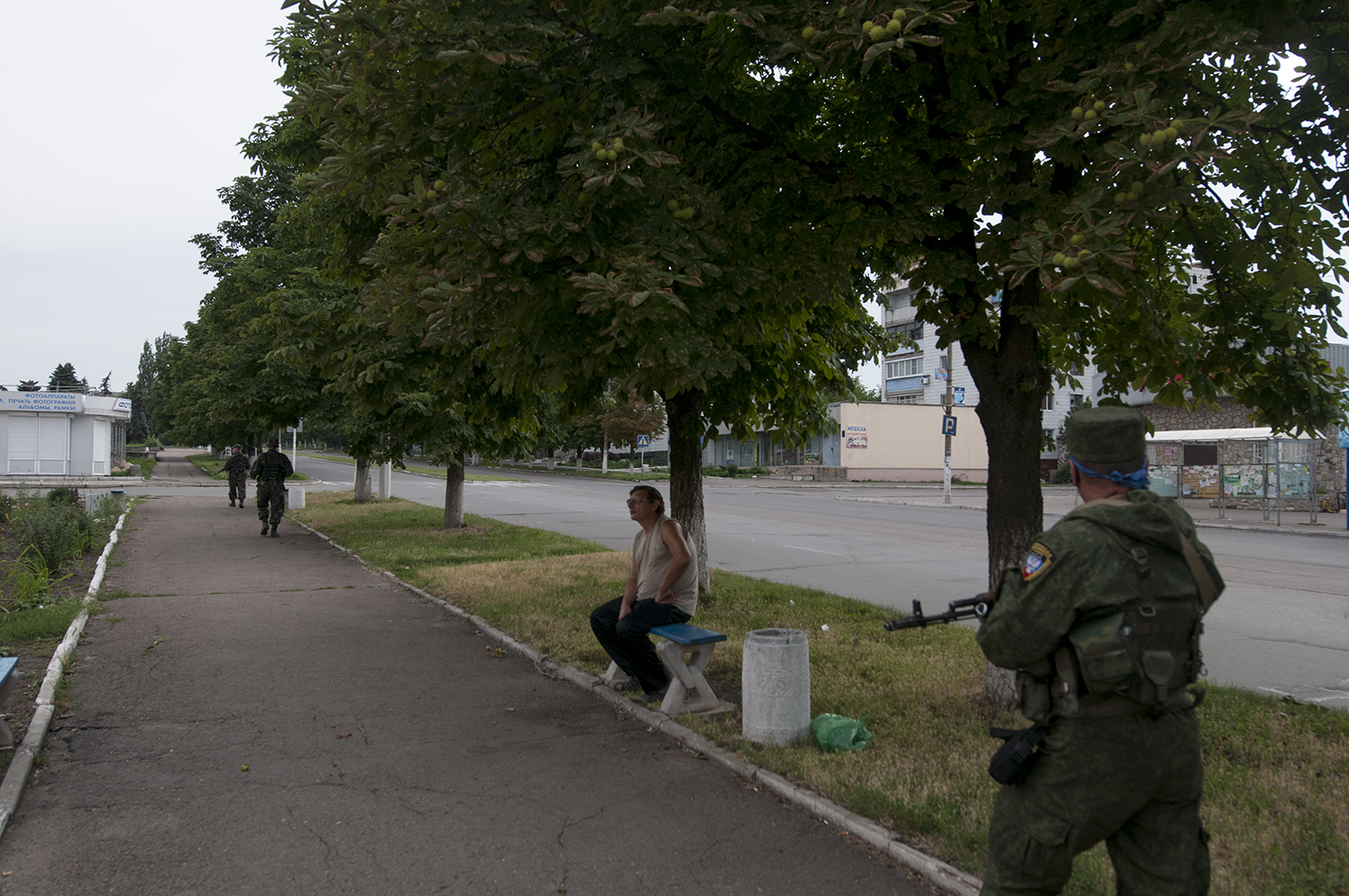 Man sitting on a bench located in the middle of the empty town of Marinka
