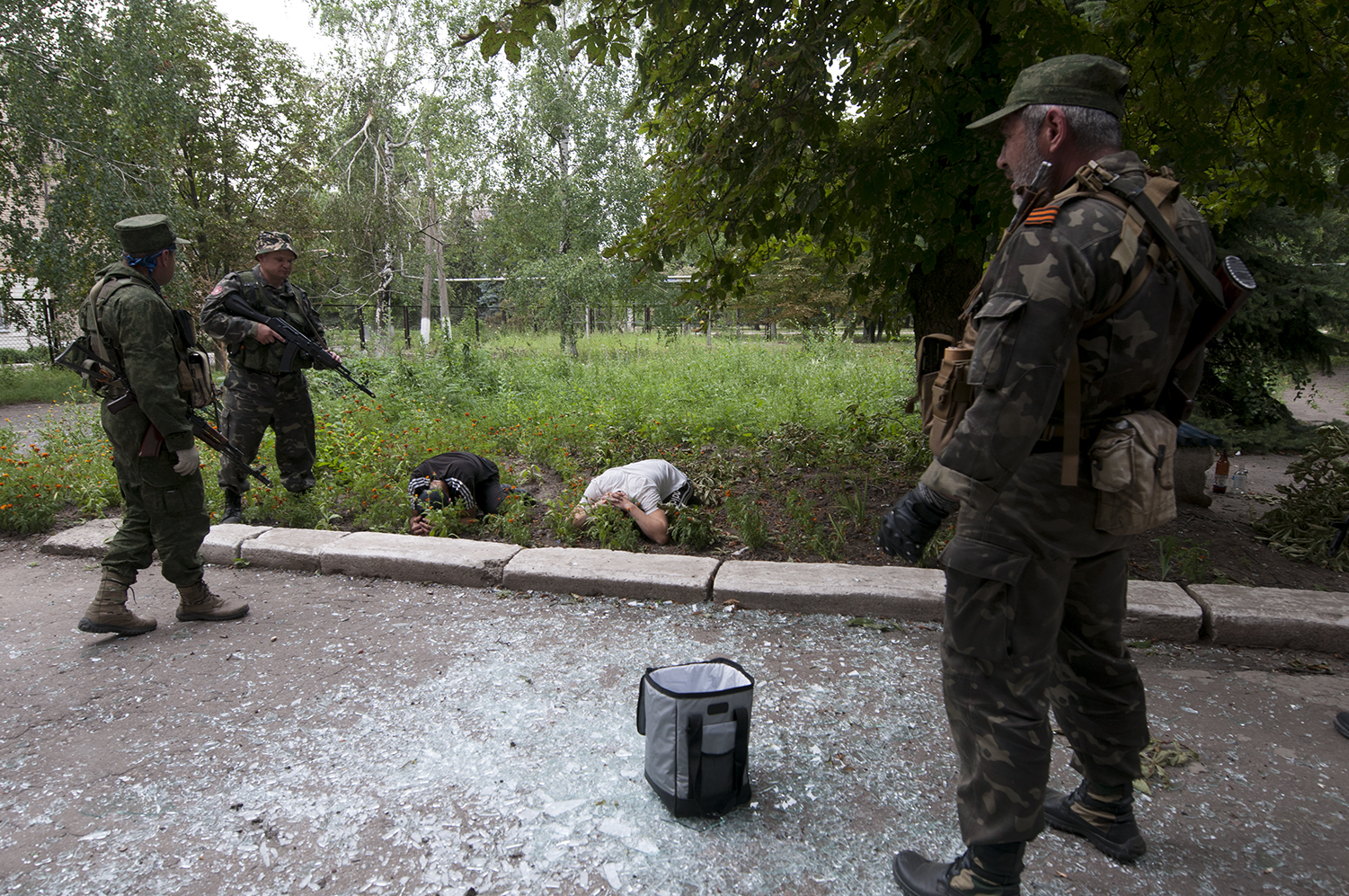 As the bag of looted goods lies in the middle of scattered pieces of glass, the two men are putting their faces against the ground after the soldiers shouted at them to do so, one of them received a kick to the ribs in the process.