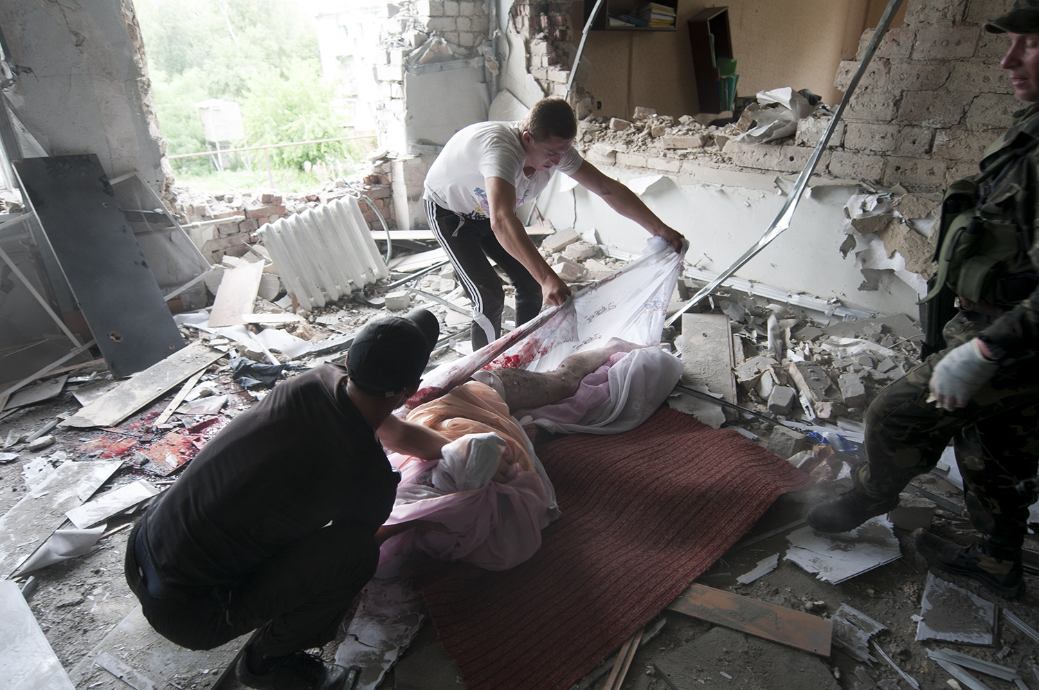 The looters struggling to move the body on a rug under the order of the separatists who arested them
