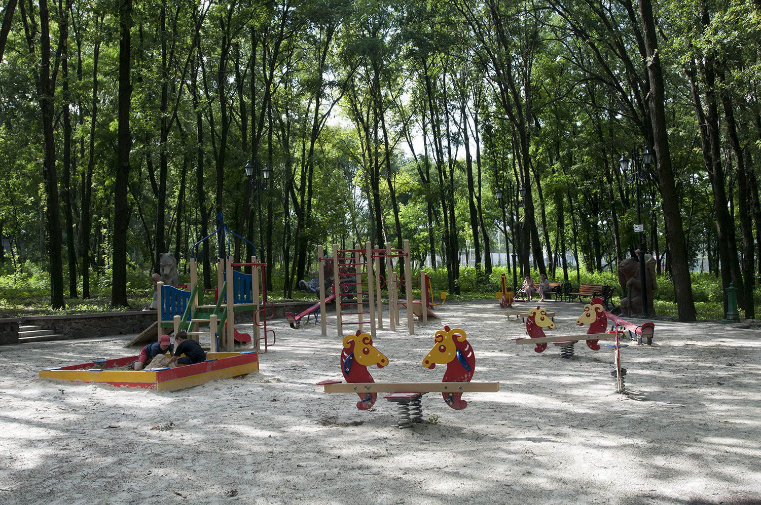 Two young boys playing in a sandbox as their mothers chat on a bench on the edge of the playground,. A few hours later a column of various military vehicles drove on the road adjacent to  this park. The convoy allegedly came from Russia  and made their way through Luhansk.