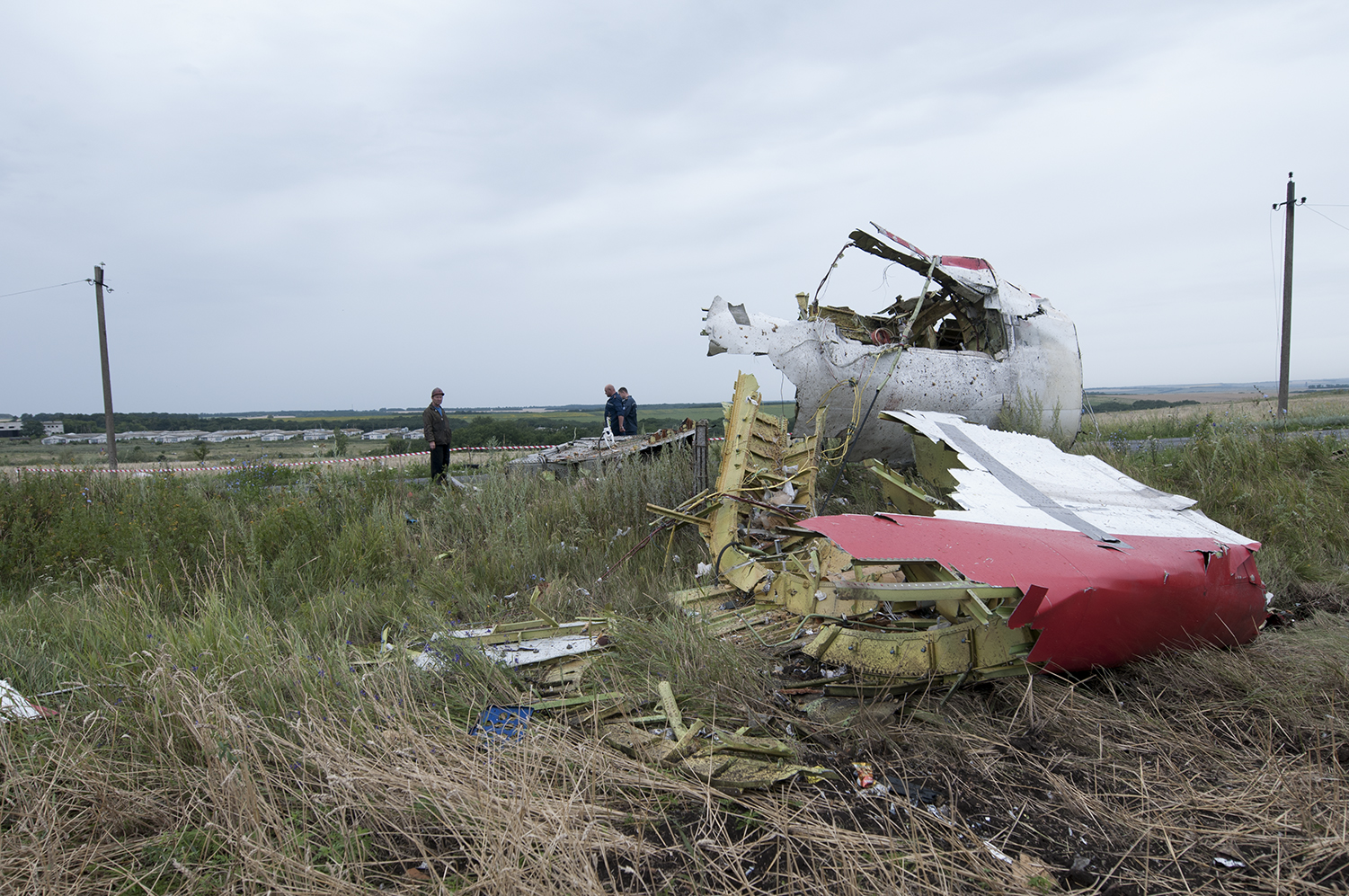 Civilians near a part of the fuselage belonging to the Boeing-777 which got shot down the 17th of July during the afternoon. The aircraft was carrying 298 people, including 15 crew members.