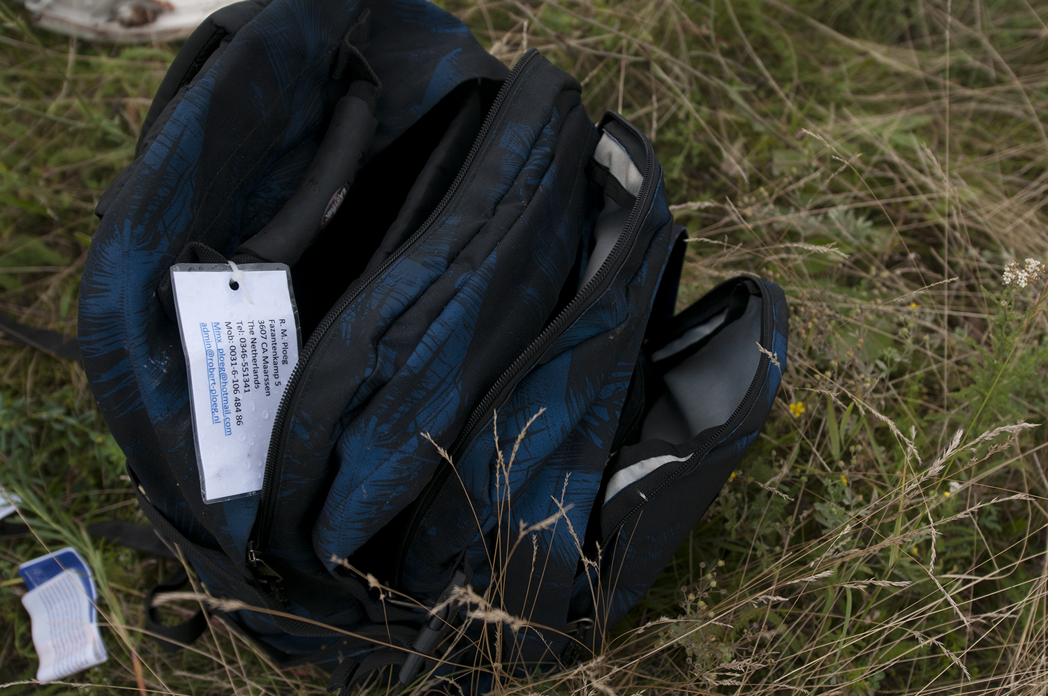 An open and empty bag belonging to one of the passengers sitting on the ground, some looting have been reported on the crash site during the night.