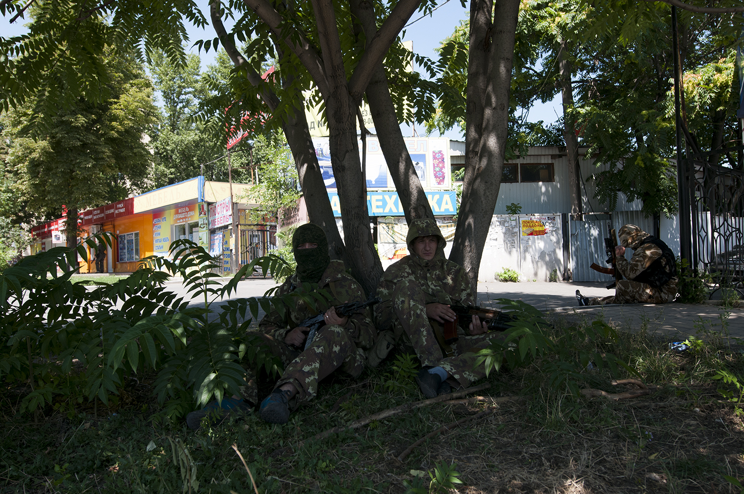 Armed men waiting in the shade