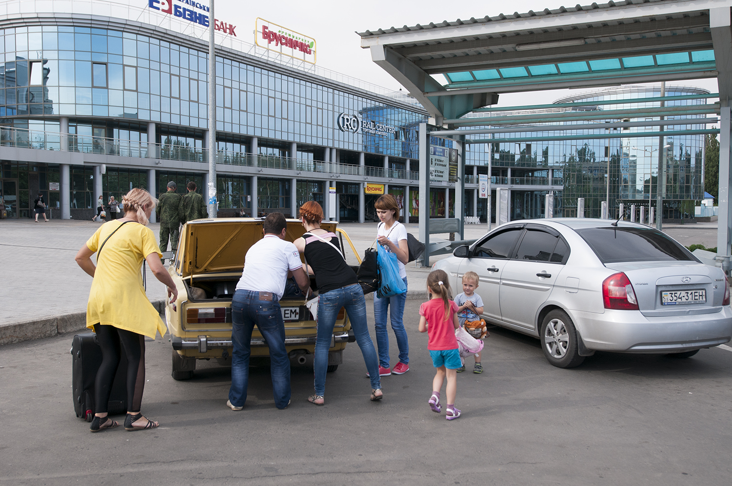 A family rushing to put their suitcases in the trunk of the car before leaving the train station