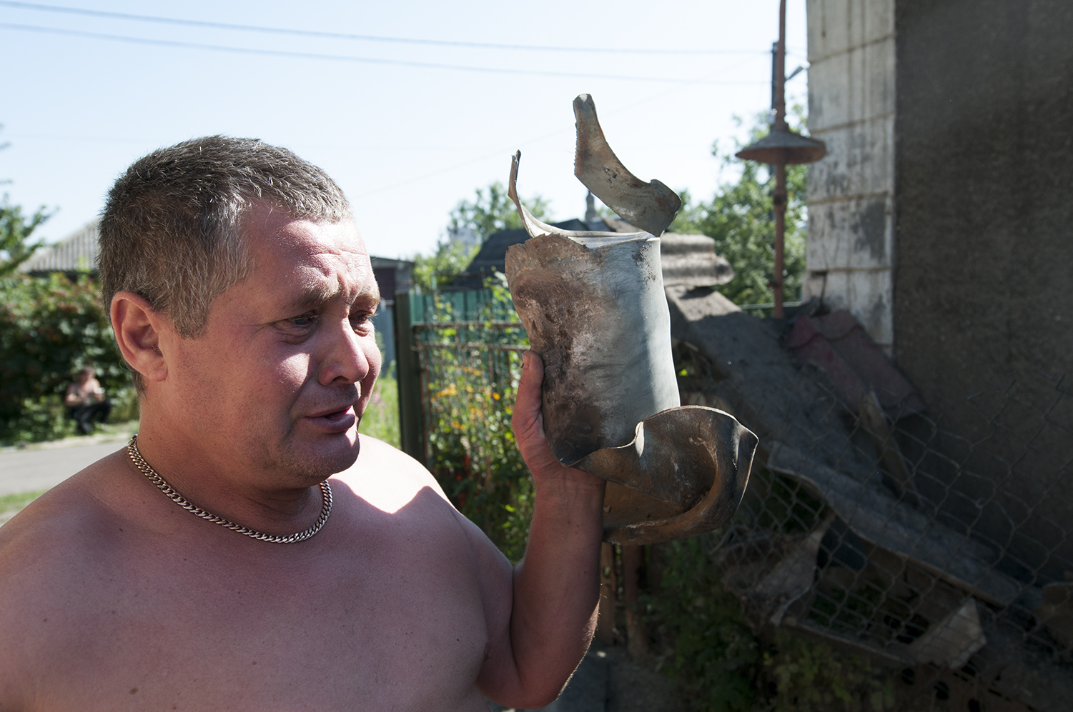 A crying man holding on to the piece of the GRAD rocket that destroyed his house a few hours before - 29th July