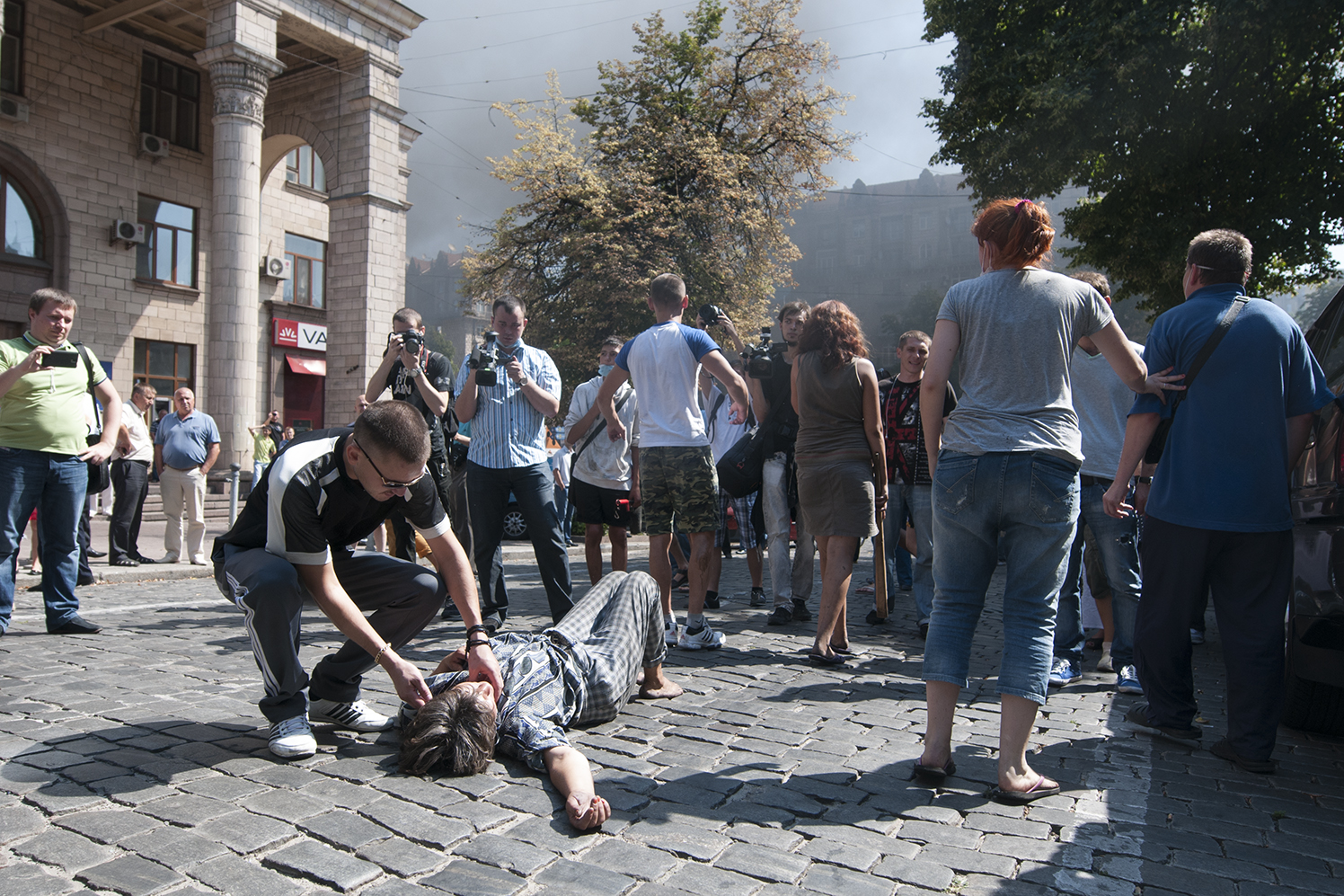 Man checking on a woman that decided to lie on the ground between the protesters and the National Guard after she the first the first that they were all brothers coming from Maidan in order to prevent an escalation of the riot