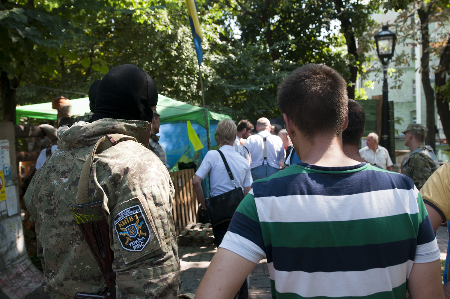 A solider from Kyiv 1 standing next to a civilian outside of Maidan Square