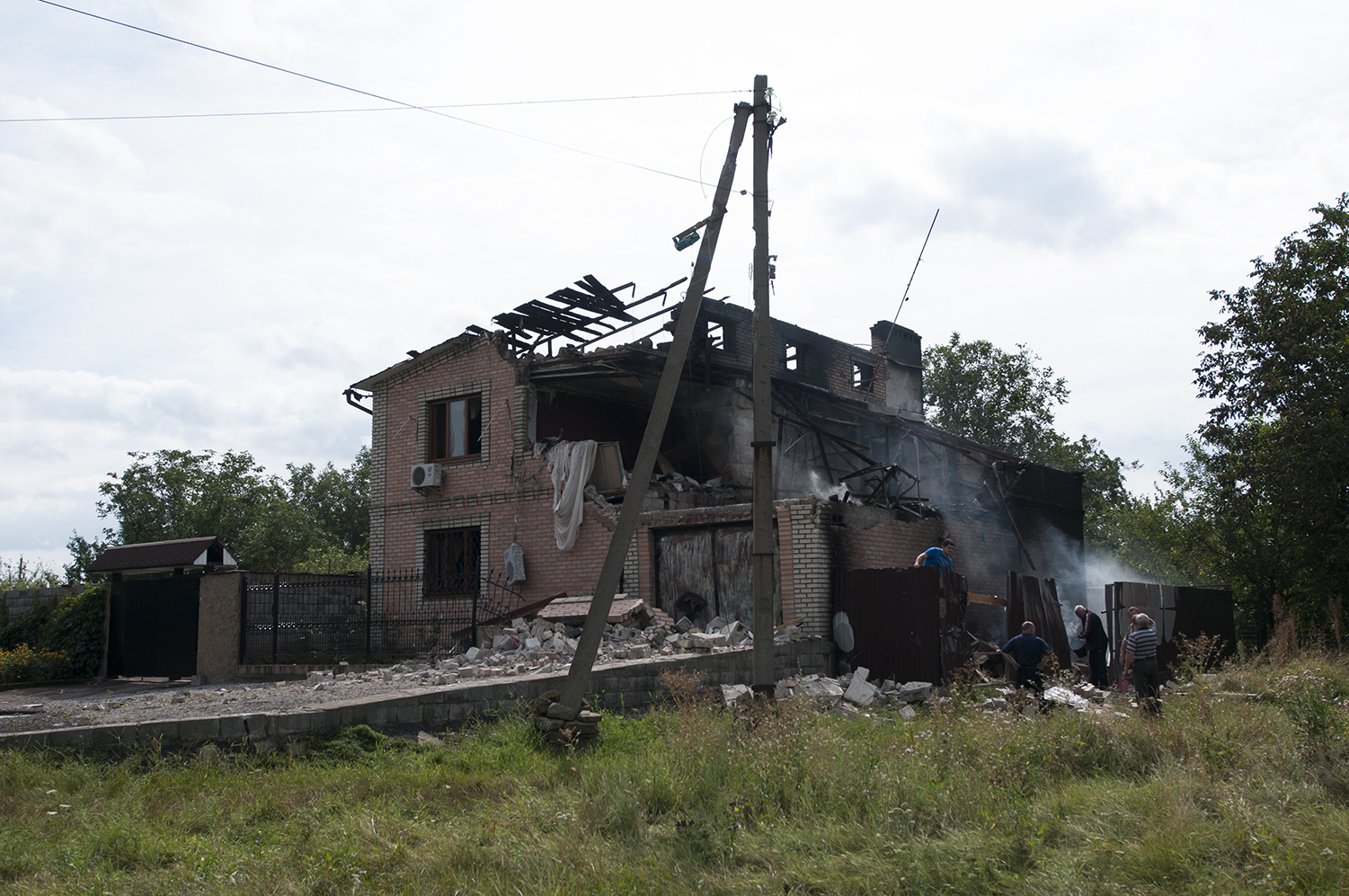 Men pulling out debris out of a house three hours after it got hit by artillery fire.The locals blamed the damages on Putin and reported the presence of a DNR compound nearby
