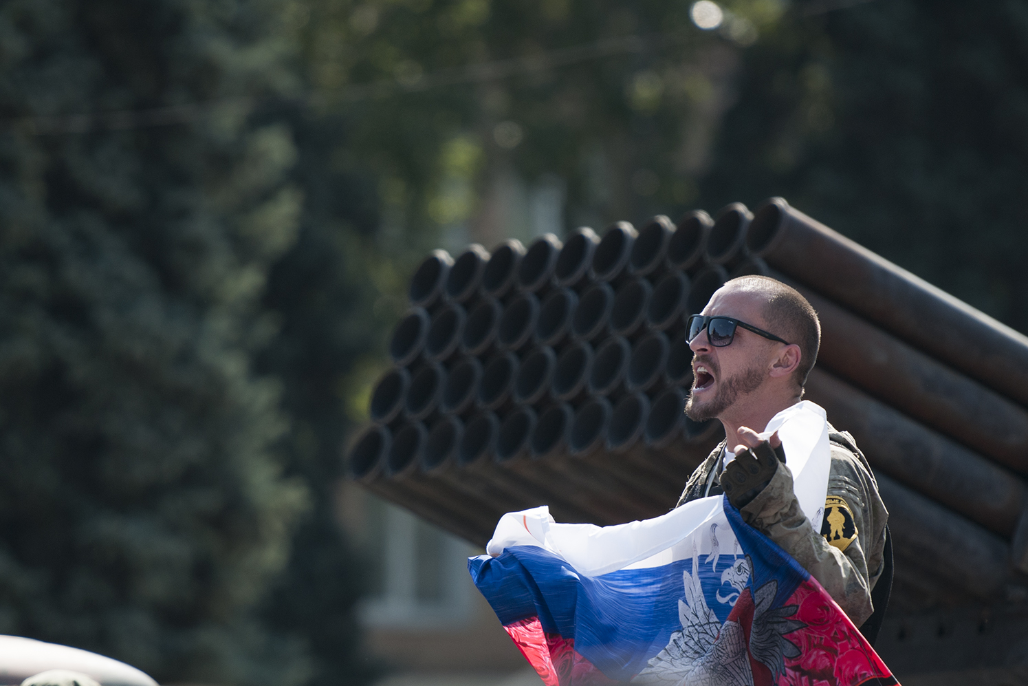 DNR soldier cheering in front of a BM-21 remains