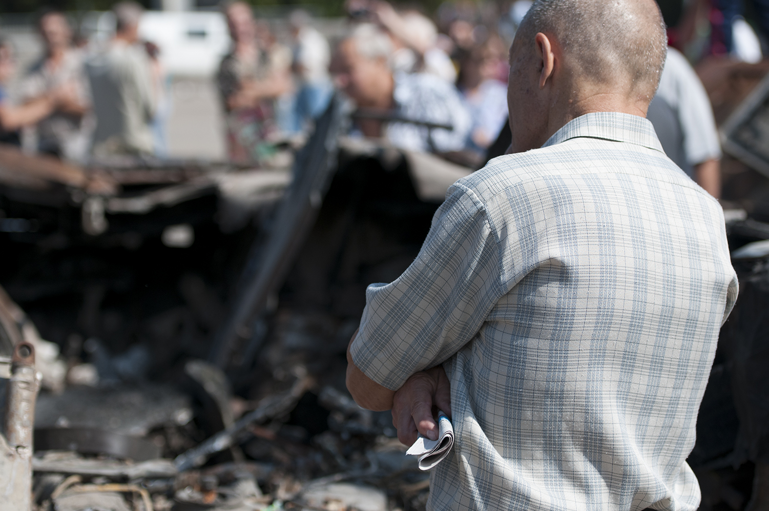An old man looking over the remains of a UKrainian APC